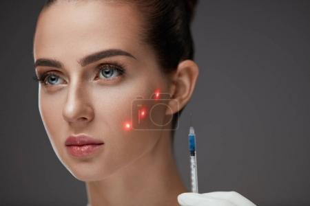Photo pour Injection beauté. Belle visage de femme avec des points laser rouges sur la peau recevant des injections de peau faciale. Gros plan de la main avec seringue faisant ponction hyaluronique. Traitement cosmétique. Haute résolution - image libre de droit