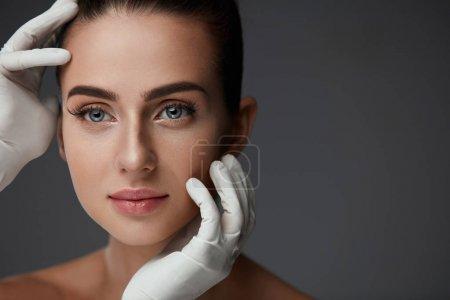 Photo pour La cosmétologie. Portrait de belle femme avant l'opération de chirurgie plastique avec les mains dans les gants touchant son visage de beauté. Gros plan de jeune femme en bonne santé avec une peau douce et lisse. Haute résolution - image libre de droit