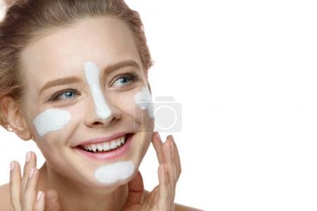 Photo pour Soins de la peau. Gros plan de jolies filles en bonne santé mettant des rayures de masque d'argile blanche sur la peau du visage. Portrait de belle jeune fille avec maquillage naturel et peau douce. Cosmétiques de beauté. Haute résolution - image libre de droit