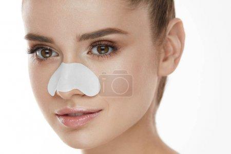 Photo pour Belle femme visage avec peau soins Patch sur le nez. Portrait de jeune femme avec le nettoyage des pores bande sur une peau propre douce. Gros plan d'une fille Sexy avec maquillage naturel et produit de beauté. Haute résolution - image libre de droit