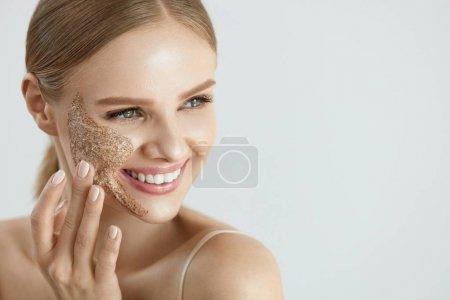 Photo pour Visage soins de la peau. Closeup Portrait de belle femme souriante heureuse avec nettoyage de masque gommage du visage sur la joue. Haute résolution - image libre de droit