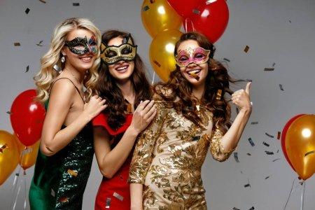 Photo for Party. Beautiful Women In Masks Celebrating New Year. Portrait Of Beautiful Happy Girls In Festive Carnival Masks And Stylish Colorful Dresses Having Fun At Party. High Resolution - Royalty Free Image