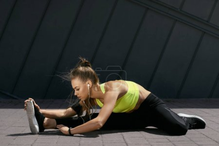 Photo for Woman Stretching Body, Doing Exercises On Street. Beautiful Athletic Girl With Fit Body In Bright Sportswear Warming Up, Doing Stretches Before Fitness Workout Outdoors. High Resolution - Royalty Free Image