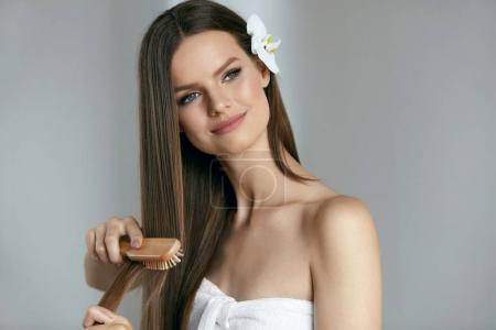 Photo for Long Hair. Beautiful Girl With Brown Healthy Hair. Portrait Of Smiling Female Model With Natural Makeup, Fresh Smooth Skin Brushing Her Straight Hair With Wood Brush. High Quality Image. - Royalty Free Image
