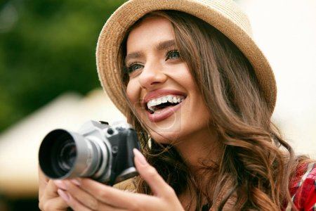 Photo for Close Up Of Smiling Tourist Woman Taking Photos On Trip. Coseup Of Happy Girl With Beautiful Smile And Gorgeous Face In Stylish Hat Taking Photo On Camera Outdoors. High Quality Image. - Royalty Free Image
