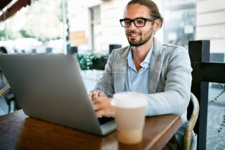 Photo for Man Working On Notebook From Cafe Outdoors. Portrait Of Stylish Successful Business Man In Modern Men Clothes Drinking Cup Of Hot Coffee While Working On Notebook Sitting At Table. High Quality Image. - Royalty Free Image