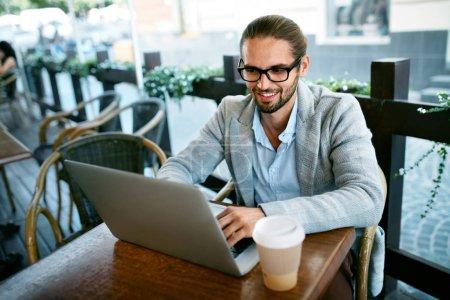 Photo pour Homme travaillant sur ordinateur portable de café en plein air. Portrait d'homme d'affaires réussi élégant dans les hommes modernes Vêtements tasse à boire de café chaud tout en travaillant sur ordinateur portable assis à la table. Image de haute qualité . - image libre de droit