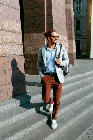 Photo pour Men Style. Un bel homme souriant sur la rue. Homme à la mode portant des lunettes et vêtements d'affaires décontractés pour hommes avec sac à dos marchant sur Sunny City Street. Vêtements de bureau et de travail. Haute qualité - image libre de droit
