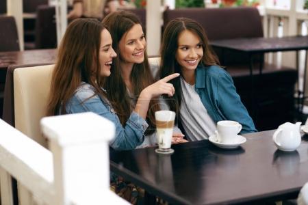 Photo pour Girls In Cafe. Des amis qui boivent du café et parlent. Jeunes femmes souriantes avec des tasses de café assis à la table dans un café confortable. Amitié féminine. Image de haute qualité . - image libre de droit