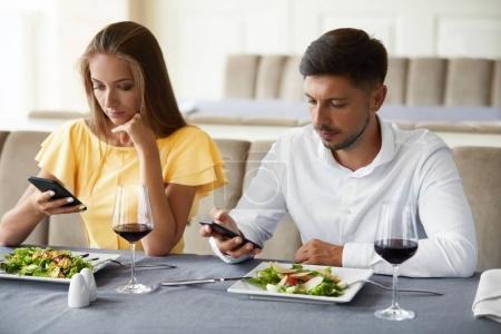 Photo pour Couple utilisant les téléphones sur le dîner au restaurant. Jeune homme et femme regardant sur les téléphones mobiles se sentant ennuyé sur la date ennuyeuse dans le restaurant. Problèmes de communication. Image de haute qualité . - image libre de droit
