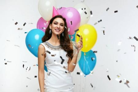 Photo for Beautiful Woman Celebrating Birthday And Having Fun With Balloons At Party. Smiling Girl Drinking Champagne With Balloons And Flying Confetti On Background. Holiday Celebration. High Quality Image. - Royalty Free Image