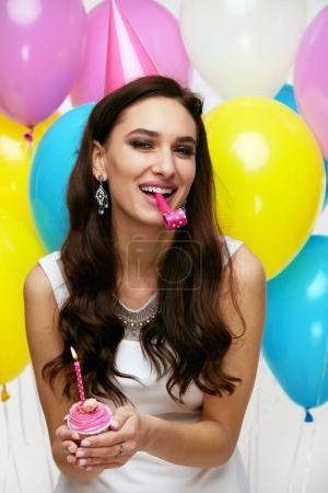 Photo for Birthday Party. Happy Beautiful Woman Celebrating With Balloons. Portrait Of Attractive Smiling Girl In Festive Hat Blowing Whistle, Holding Cupcake And Celebrating Holiday. High Resolution - Royalty Free Image