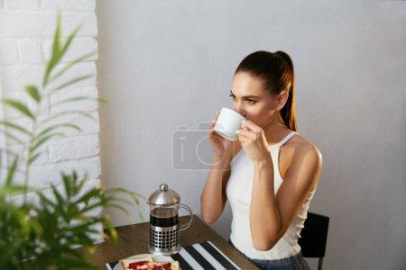 Photo pour Femme buvant du café et prenant le petit déjeuner le matin sur la cuisine. Belle fille heureuse appréciant la nourriture et boire assis à la table dans la salle à manger. Image de haute qualité . - image libre de droit
