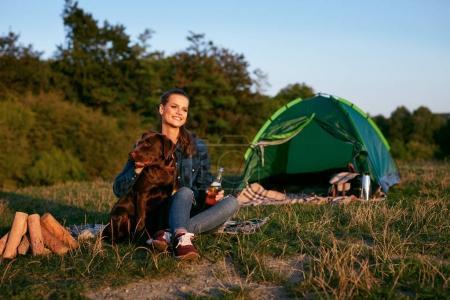 Foto de Mujer feliz de viajar con perro en fin de semana en la naturaleza. Hermosa niña sonriente sentado junto a la tienda de campaña con cerveza y hoguera, pasar tiempo junto a su mascota de viaje vacaciones. Imagen de alta calidad. - Imagen libre de derechos