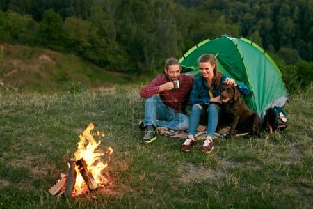 Photo for Man And Woman Traveling With Dog At Camp. Happy Couple Travel With Dog In Nature. Smiling Young People Sitting Near Camping Tent And Playing With Pet, Traveling On Weekend. High Quality Image - Royalty Free Image