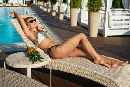 Photo for Summer. Beautiful Girl In Fashion Bikini Relaxing Near Pool. Beautiful Sexy Woman With Fit Body And Healthy Tan Skin In Fashionable Swimwear Sunbathing And Enjoying Vacation At Resort. High Quality - Royalty Free Image