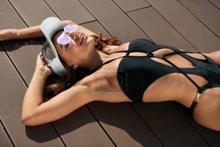 Photo for Fashion Woman In Swimsuit Relaxing In Summer. Beautiful Female Model With Tanned Healthy Skin And Sexy Fit Body In Trendy Sunglasses And Stylish Swimwear Lying Near Pool. High Quality Image. - Royalty Free Image
