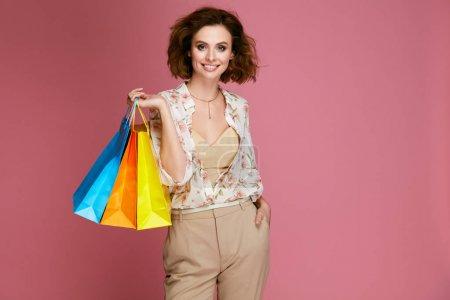 Photo pour Mode. Femme de sacs de vêtements à la mode sur fond rose. Heureux souriant jeune modèle féminin en vêtements portant les sacs papier coloré. Style de femmes. Haute qualité d'Image. - image libre de droit