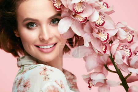 Photo for Beauty Makeup. Beautiful Woman Face With Flowers. Gorgeous Smiling Young Female Model With Fresh Facial Makeup, Clean Soft Skin And Perfect Smile Holding Pink Flower Near Face. High Quality Image. - Royalty Free Image