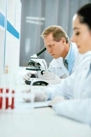 Photo for Scientists In Laboratory. Medical Workers At Work. Mature Male Doctor Researching Using Microscope While Female Scientist Working In Modern Laboratory. Medical Lab. High Quality - Royalty Free Image
