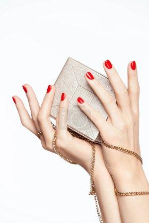 Photo pour Beauté ongles. Femmes mains avec manucure rouge. Gros plan des mains de femme avec du vernis à ongles rouge tenant bourse de mode sur fond blanc. Haute résolution. - image libre de droit