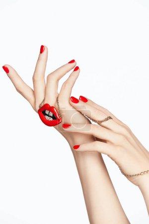 Photo pour Nails Design. Mains avec manucure rouge et les lèvres rouges. Gros plan d'une main féminine avec une peau douce et vernis à ongles rouge tenant des accessoires de mode lèvres rouges sur fond blanc. Haute résolution. - image libre de droit