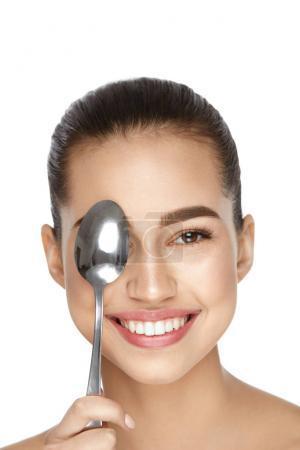 Photo pour Soins de la peau des yeux. Belle femme avec une peau saine détenant une cuillère froide près de œil sur fond blanc. Haute résolution. - image libre de droit