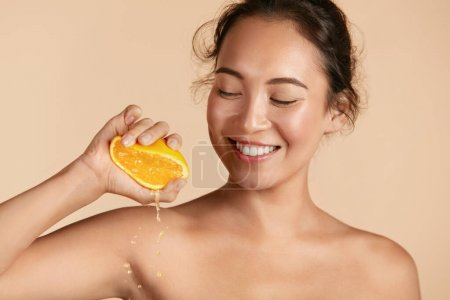 Photo for Beauty. Woman with radiant face skin squeezing orange in hand portrait. Beautiful smiling asian girl model with natural makeup, glowing facial skin and citrus fruit. Vitamin C cosmetics concept - Royalty Free Image