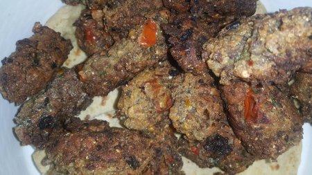 Photo pour Vue de plan rapproché avec l'accent sélectif sur le kebab rond frit délicieux servi dans une plaque en céramique - image libre de droit
