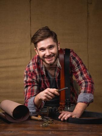 handsome bearded man in red shirt with leather on wooden table