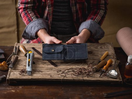 close-up of male hands sew leather wallet on wooden table