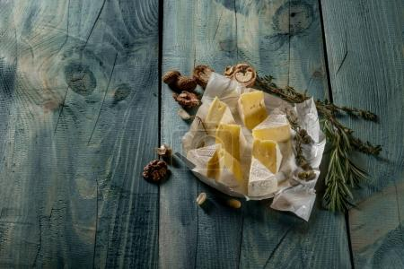 brie cheese slices, herbs and nuts on blue wooden background, top view with copy space