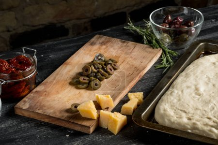 cooking pizza concept with olives, cheese and salami