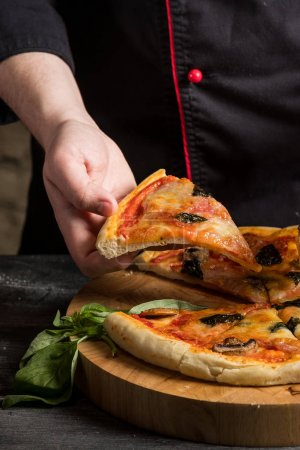 close up of male hand holding delicious pizza slice