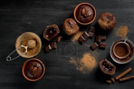 gâteaux de lave sucrés et morceaux de chocolat sur fond en bois noir avec ustensile, vue de dessus