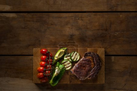 top view of grilled vegetables and meat on wooden table with copy space
