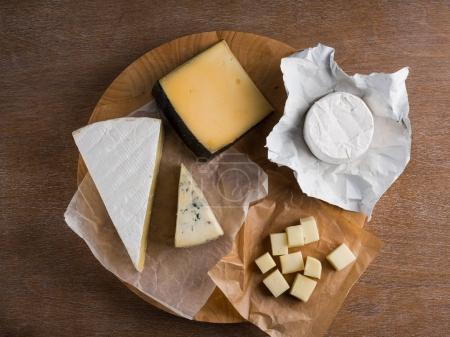Photo for Assorted cheese slices on wooden board, top view - Royalty Free Image