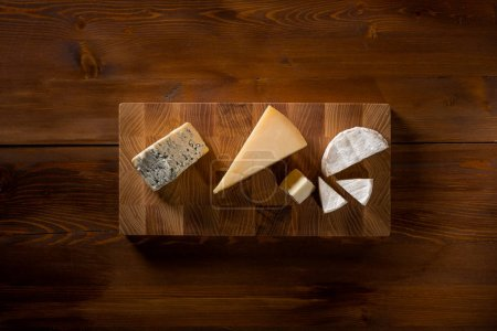 various delicious cheeses slices on wooden board, top view