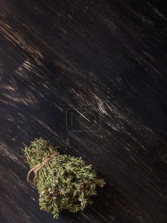 close-up of green dry herbs on black wooden table