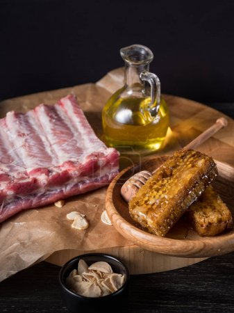 close-up of raw Beef Ribs with dry herbs and glass jar of olive oil on parchment paper background