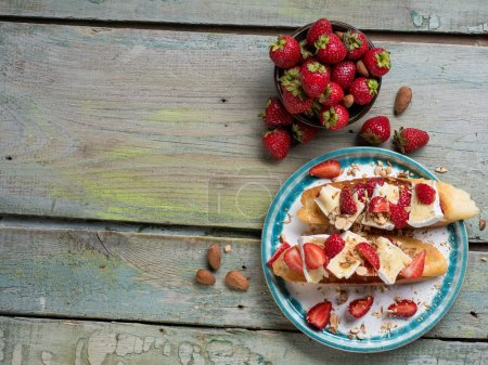 Sweet bruschetta with strawberries, cheese, camembert on the whole grain roasted bread - on wooden blue light background