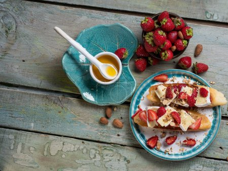 Photo for Cooking bruschetta with strawberry, nuts and cheese camembert on wooden blue rustic background. Top view, flat lay, from above - Royalty Free Image