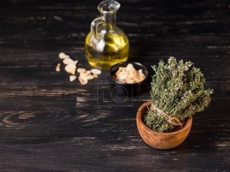 close-up of green dry herbs in wooden bowl with olive oil on black table