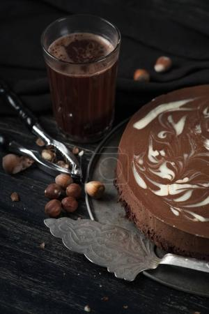 close-up of tasty chocolate cake with nuts on metal tray with nuts cracker on wooden table