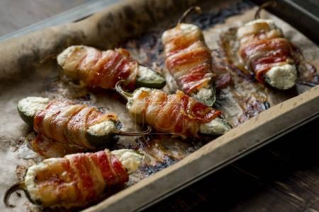 Photo pour Piments jalapeno cuits au four, farcis au fromage et au bacon. Recette alimentaire sur fond en bois. Gros plan - image libre de droit