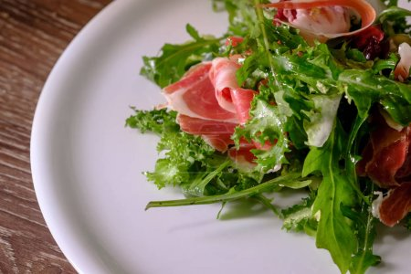 close-up of fresh salad with green leaves of arugula and bacon on white plate