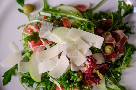 close-up of fresh salad with green leaves of arugula with parmesan cheese and bacon on white plate