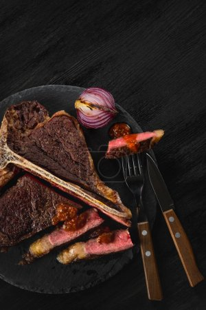grilled meat with spices on black plate background