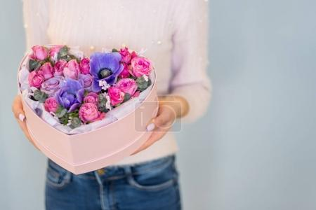 female hands holding pink heart shaped gift box with color flowers