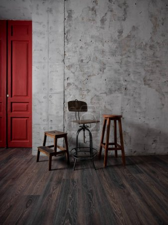 Photo for Vintage wooden chairs in room with grey concrete wall and red door - Royalty Free Image